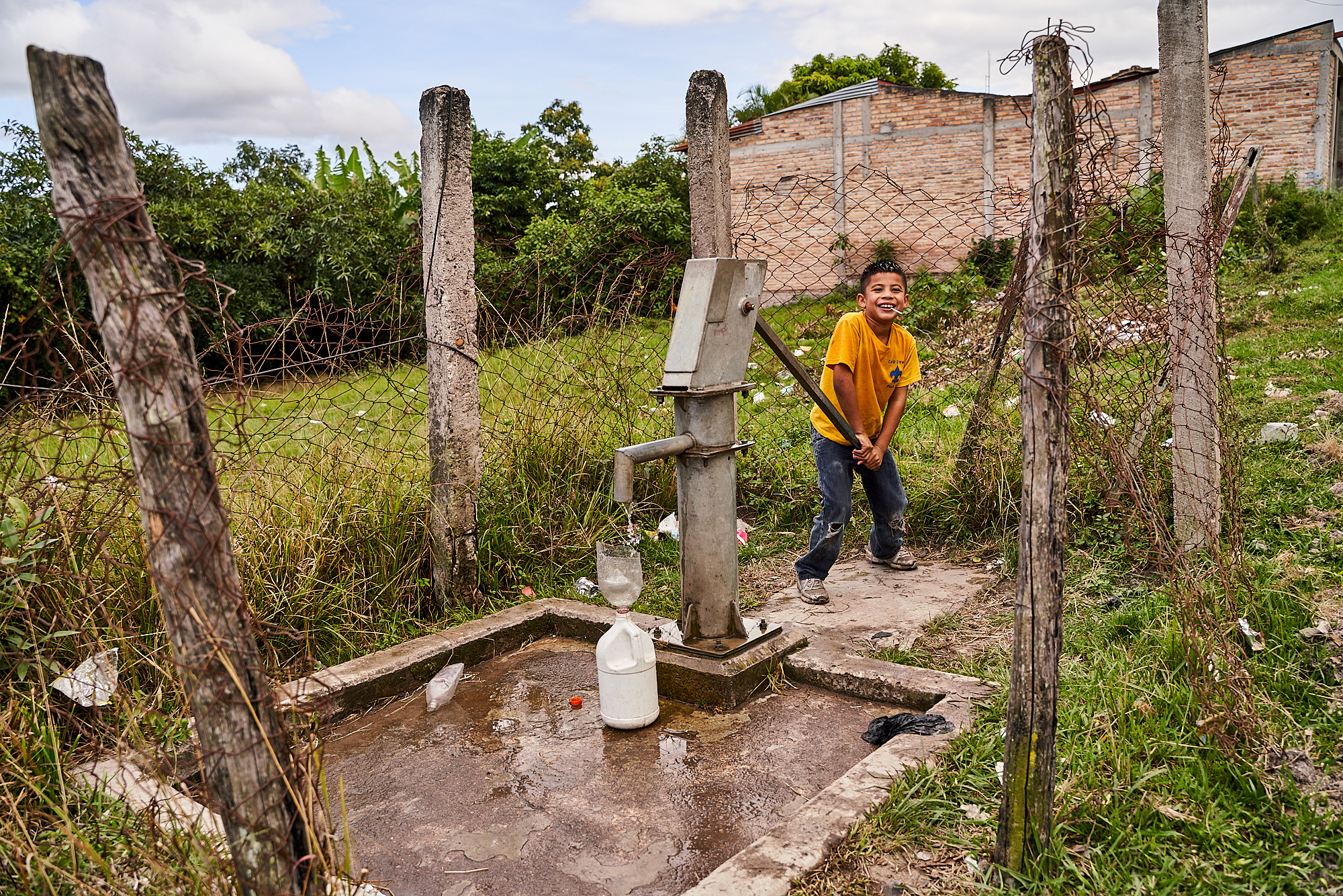 A boy pumps water at a well in Honduras.